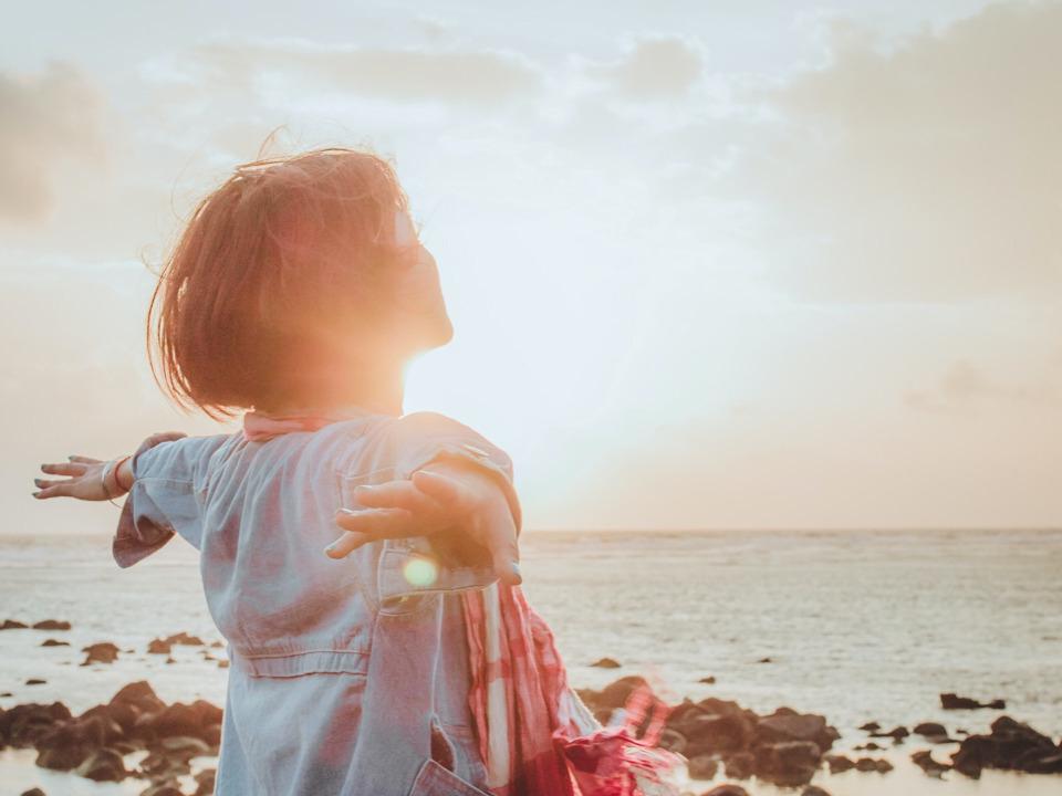 朝日を背に手を広げる少女
