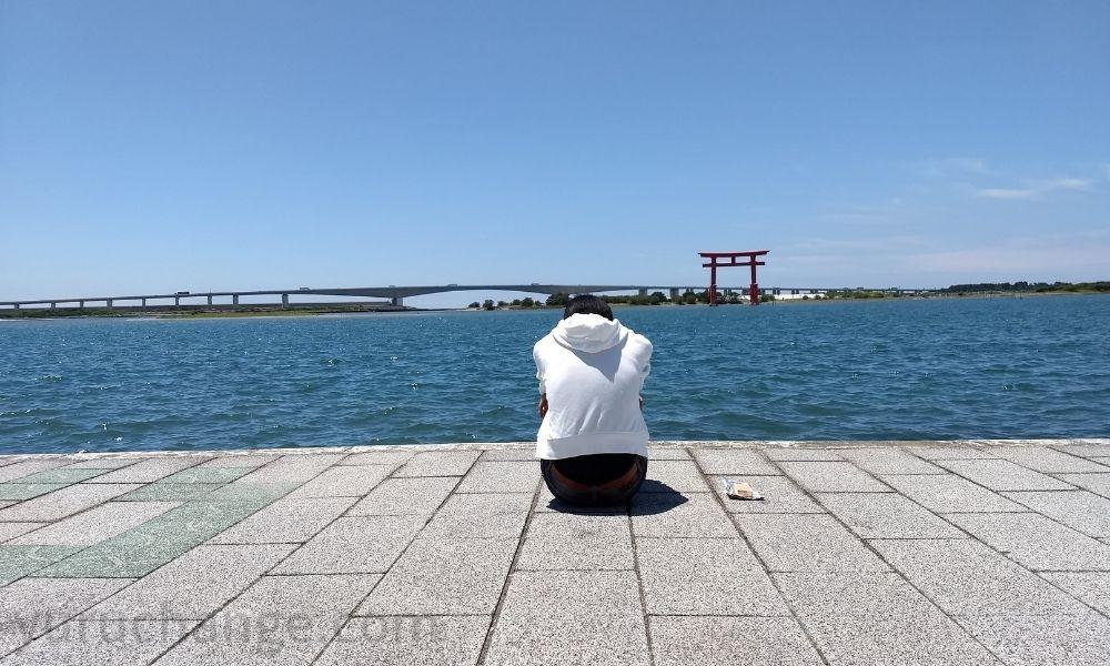 第3村で体育座りするシンジ君の再現写真 in 弁天島海浜公園